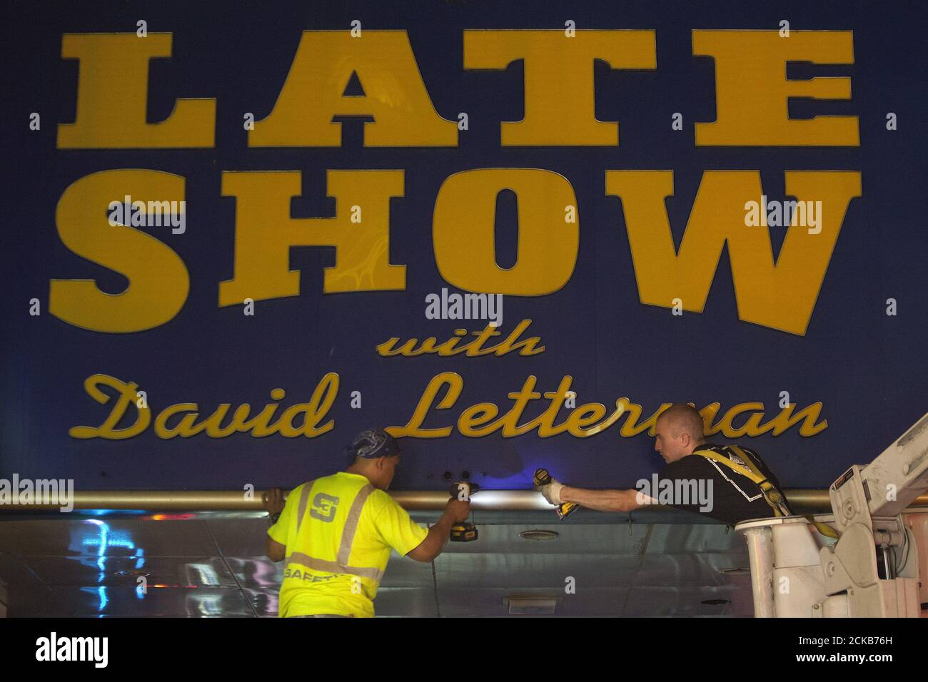 """Workers remove the marquee from the Ed Sullivan Theater where """"The Late Show"""" with David Letterman used to tape in the Manhattan borough New York May 27, 2015. The taping and broadcast of the final edition of """"The Late Show"""" was May 20, and workers are now slowly transforming the theater for the show's new host Stephen Colbert which will premiere on September 8, 2015.   REUTERS/Carlo Allegri Stock Photo"""