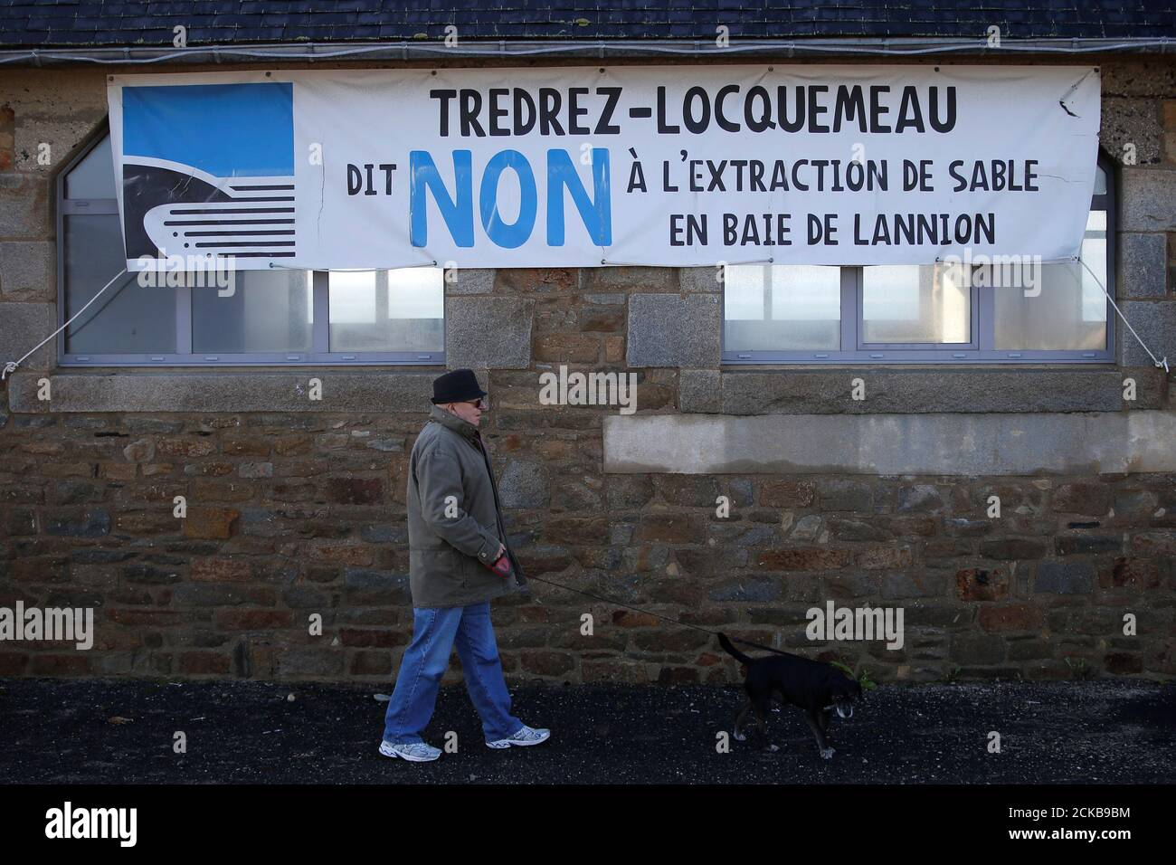"""A man walks in front of a banner which reads: """"Tredrez-Locquemeau say No to the extraction of sand in the bay of Lannion"""" in Tredrez-Locquemeau, December 17, 2016. REUTERS/Stephane Mahe Stock Photo"""