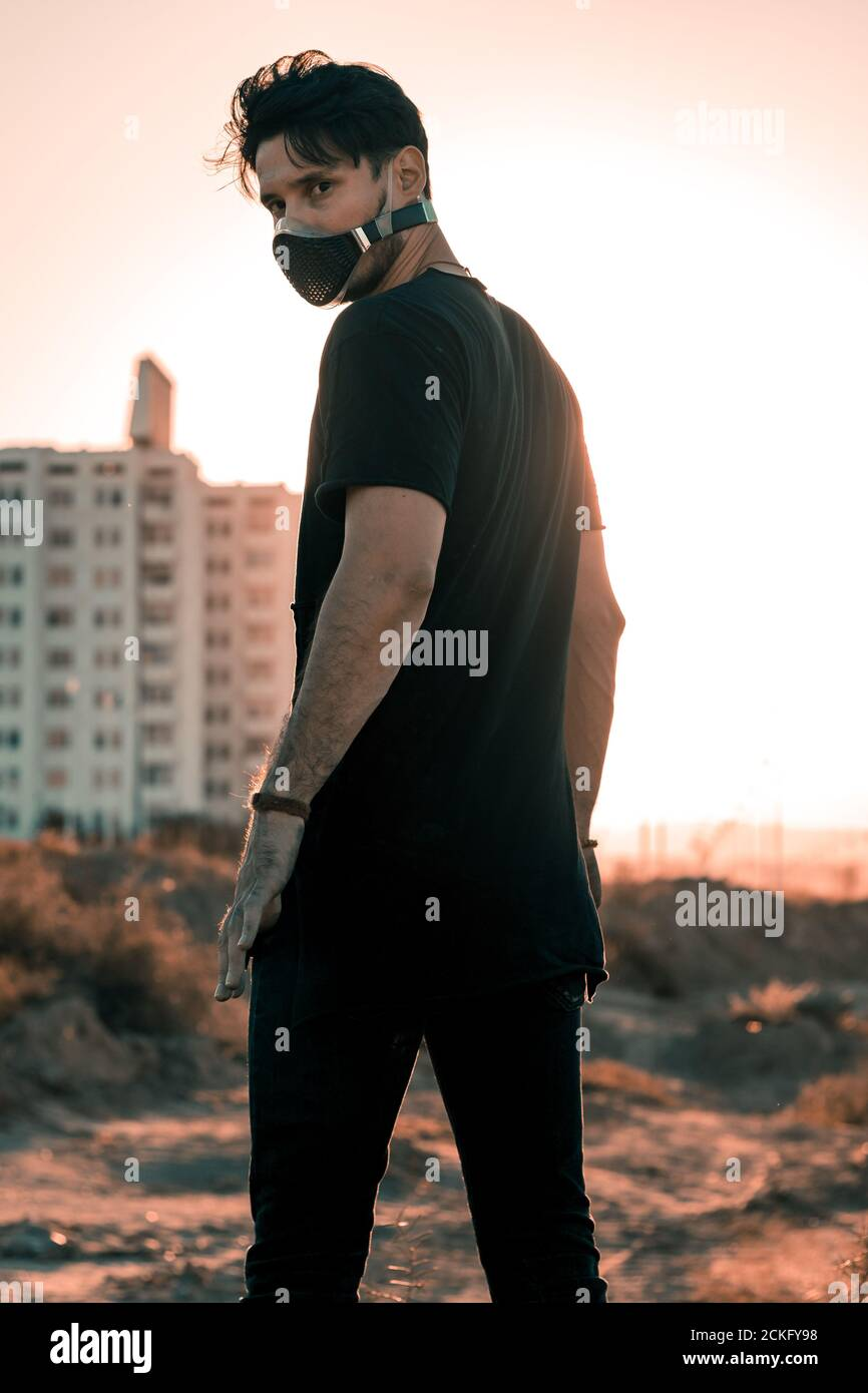 A physically distant and socially connected young man in a black outfit in an industrial zone Stock Photo