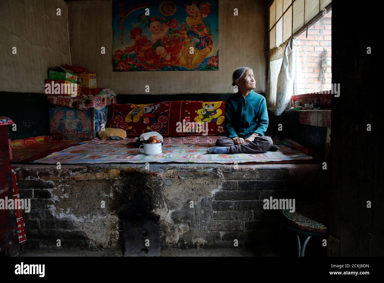 """Chinese former """"comfort woman"""" Zhang Xiantu rests on a traditional brick bed in her house in Xiyan Town, Shanxi Province, China, July 18, 2015. """"Comfort women"""" is the Japanese euphemism for women who were forced into prostitution and sexually abused at Japanese military brothels before and during World War Two. Xiantu is the only surviving """"comfort woman"""" of the 16 plaintiffs in Shanxi who sued the Japanese government in 1995 for abducting girls and using them as """"comfort women"""" during World War Two. According to information from China's Commission of Inquiry into the Facts of Comfort Women be Stock Photo"""