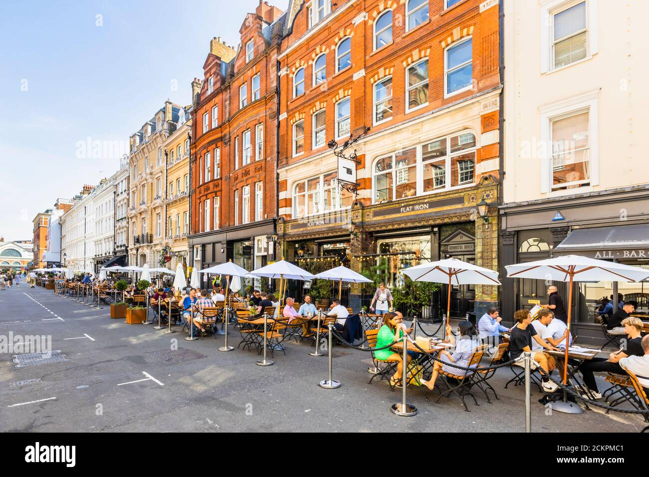 Al fresco roadside lunchtime socialising, dining, eating and drinking in pedestrianised Henrietta Street, Covent Garden, London WC2 on a sunny day Stock Photo