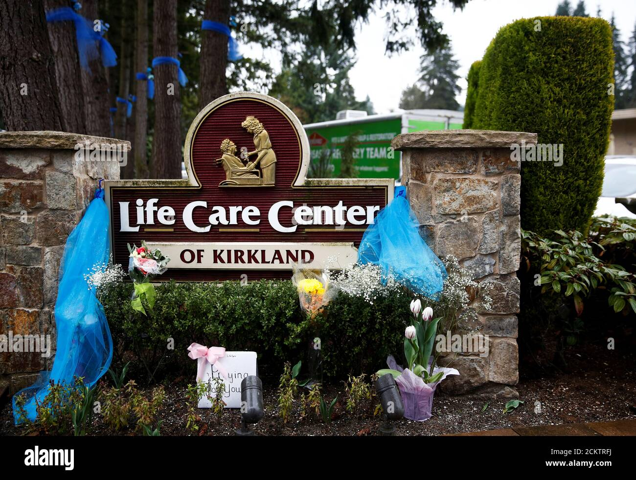 Flowers are seen near the sign outside Life Care Center of Kirkland, a long-term care facility linked to several confirmed coronavirus cases, in Kirkland, Washington, U.S. March 13, 2020.  REUTERS/Lindsey Wasson Stock Photo