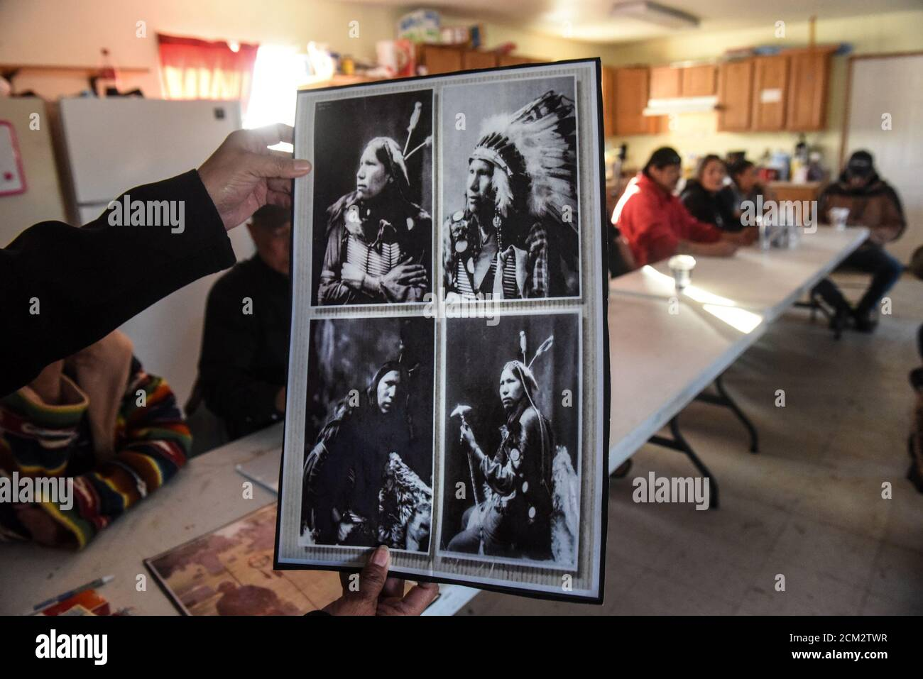 Descendant of the Lakotas killed at the Wounded Knee massacre gather at a community building while a person displays photos of an ancestor on the Cheyenne River reservation in Bridger, South Dakota, November 7, 2019.  REUTERS/Stephanie Keith Stock Photo