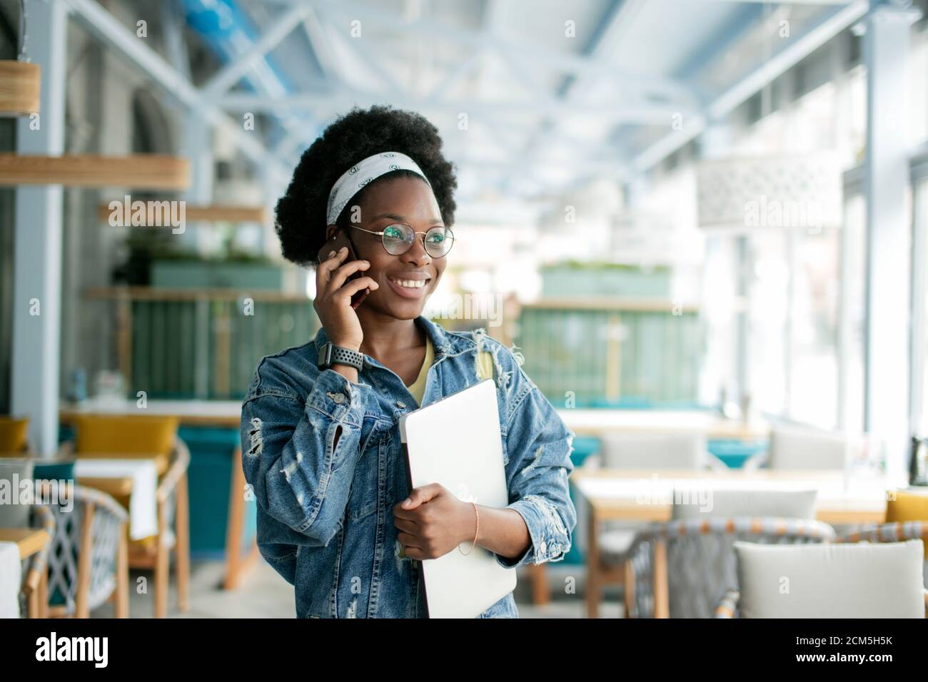 Cute dark skinned female entrepreneur holding digital tablet, making call while visiting coffee shop, inviting a candidate to a job interview. Stock Photo