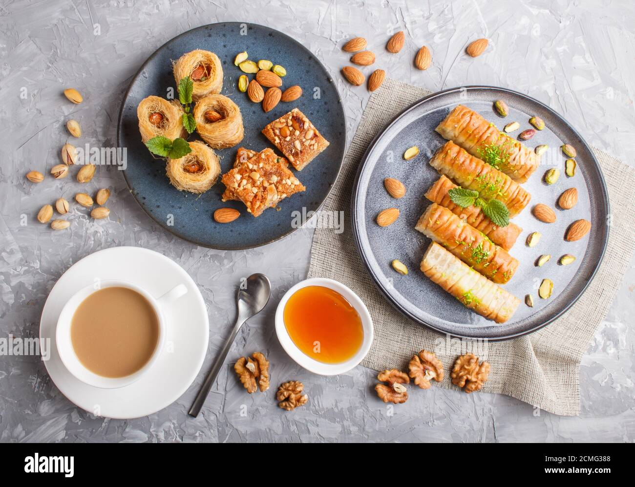 Set of various traditional arabic sweets: baklava, kunafa, basbus in  ceramic plates on a gray concrete background. top view, flat lay. Stock Photo