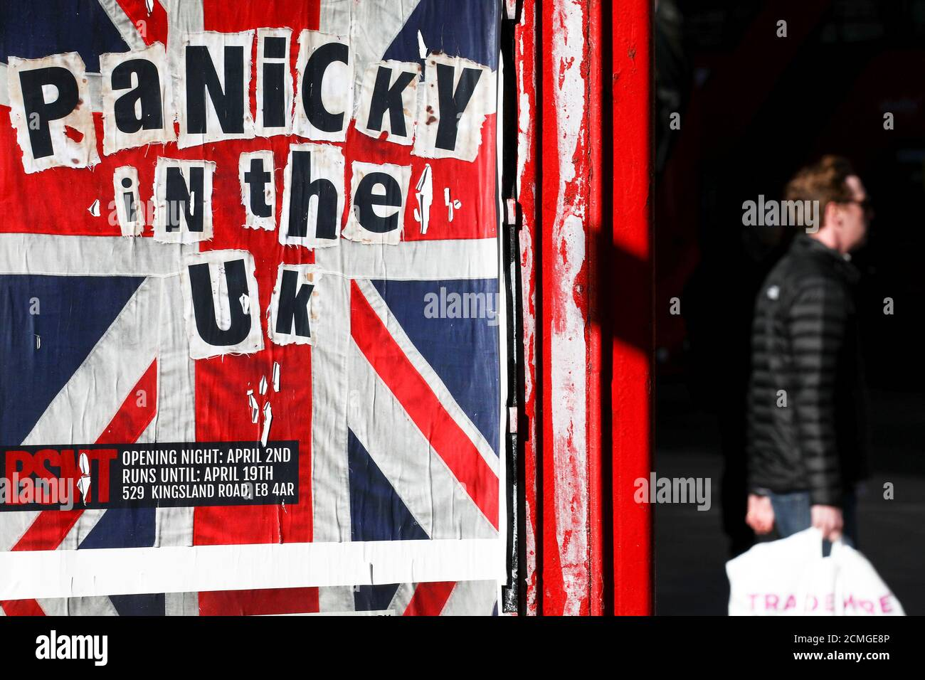 A pedestrian walks past an advertisement for 'Panicky in the UK' displayed on a phone box in the Soho district after they closed because of the spread of coronavirus disease (COVID-19), in London, Britain, March 22, 2020. REUTERS/Simon Dawson Stock Photo
