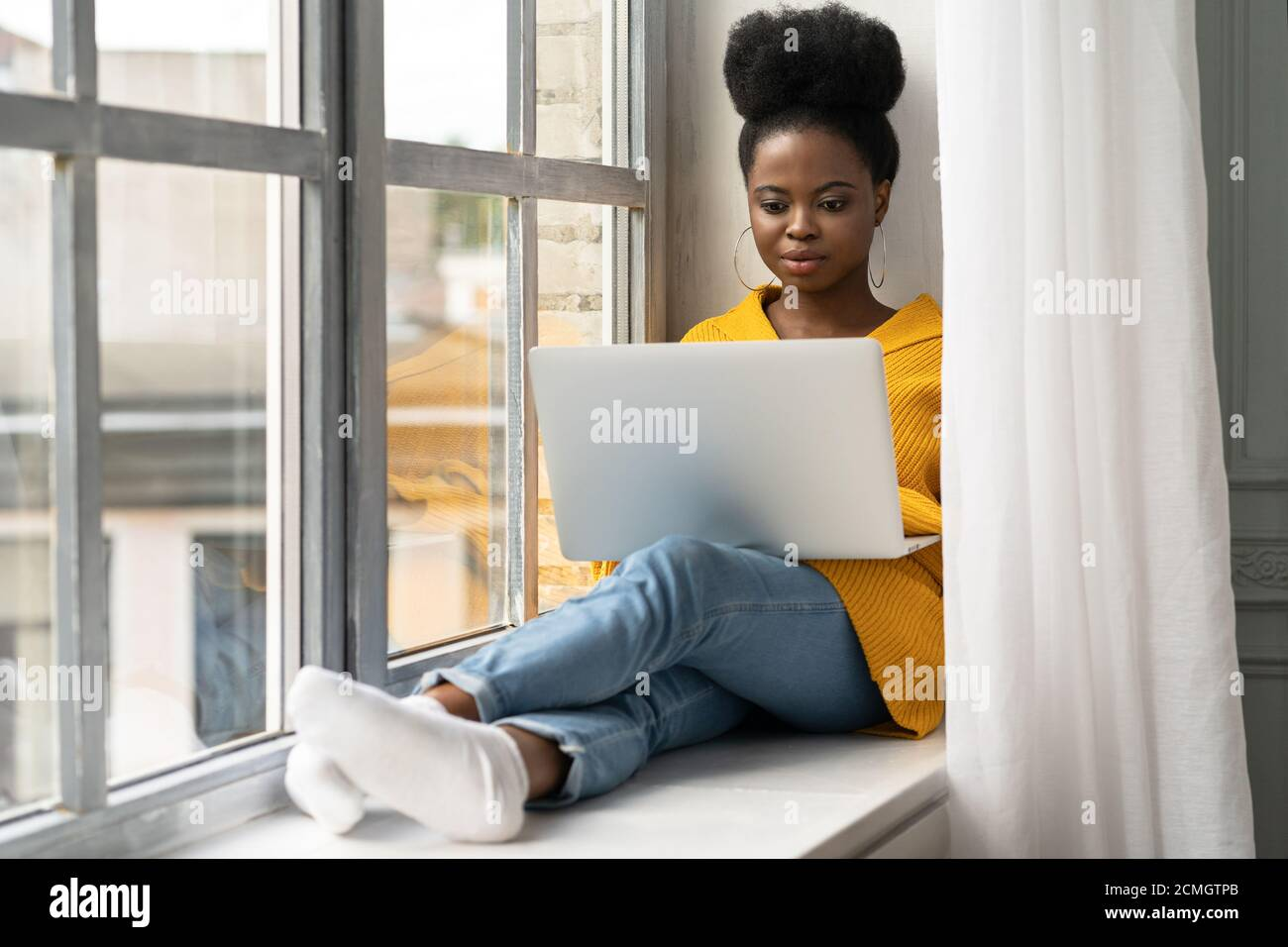 African American woman student with afro hairstyle wear yellow cardigan, sitting on windowsill, working doing remote job on laptop, learning using onl Stock Photo