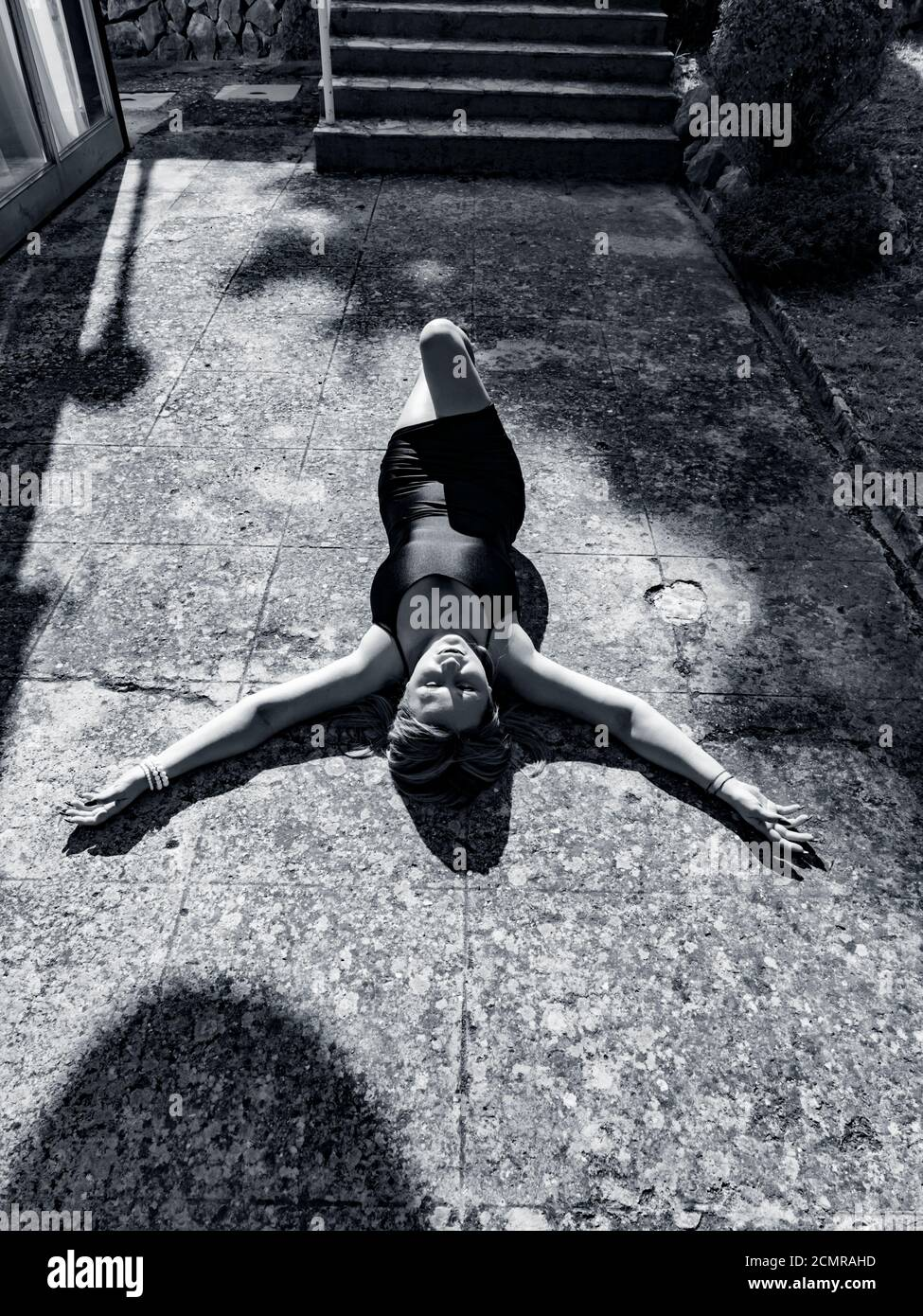 Young woman lying on her back on sunlit concrete floor ground on street before staircase with spread arms hands apart wide sunshine sunny sunlight b&w Stock Photo