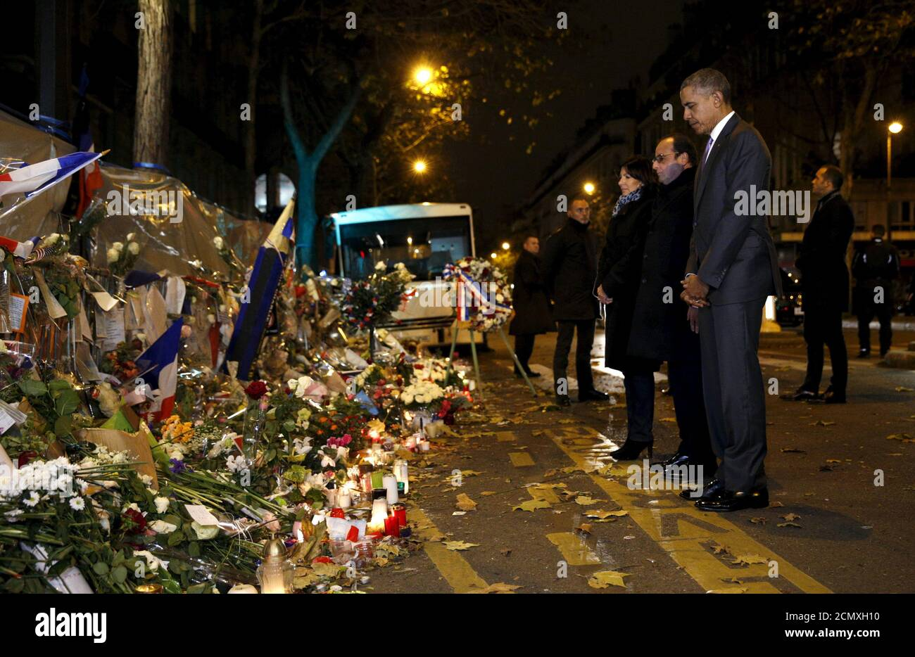 Paris Mayor Anne Hidalgo, French President Francois Hollande and U.S. President Barack Obama bow their heads as they visit a makeshift memorial to pay tribute to the victims of the Paris attacks  at the Bataclan in Paris  November 30, 2015.  REUTERS/Kevin Lamarque Stock Photo