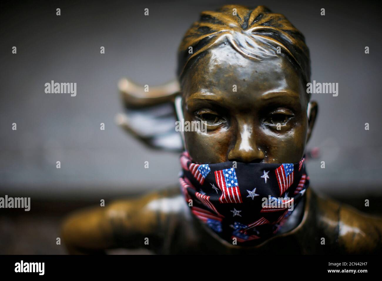 """A protective mask is seen on the face of the """"Fearless Girl"""" sculpture in the financial district, during the outbreak of the coronavirus disease (COVID-19) in New York City, New York, U.S. April 23, 2020. REUTERS/Eduardo Munoz TPX IMAGES OF THE DAY Stock Photo"""
