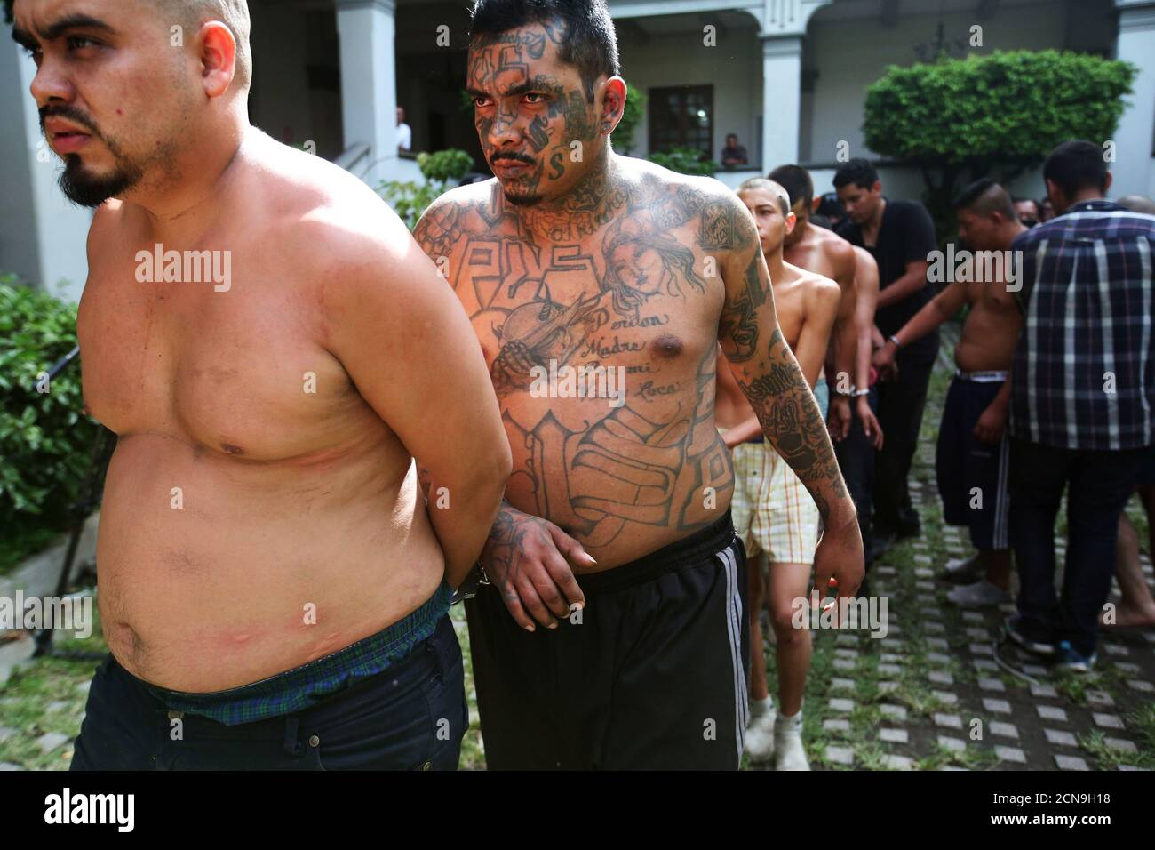Members of the Mara Salvatrucha gang (MS-13) are escorted after being presented to the media after being detained by the police during a private party in San Salvador, El Salvador, August 10, 2017. REUTERS/Jose Cabezas Stock Photo
