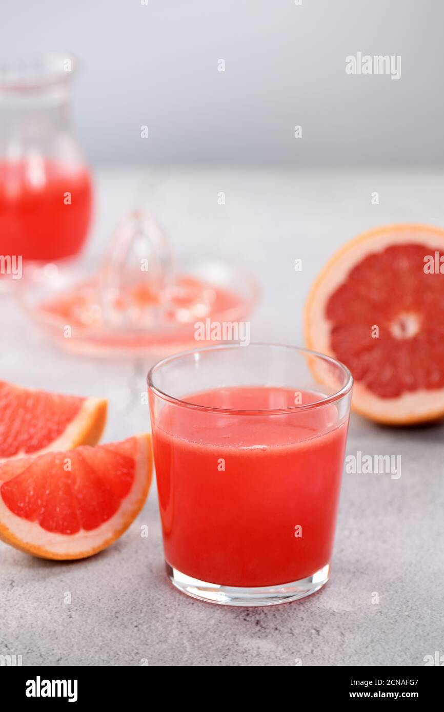 A glass of freshly made grapefruit juice and slices of fresh fruit on a light concrete background. H Stock Photo