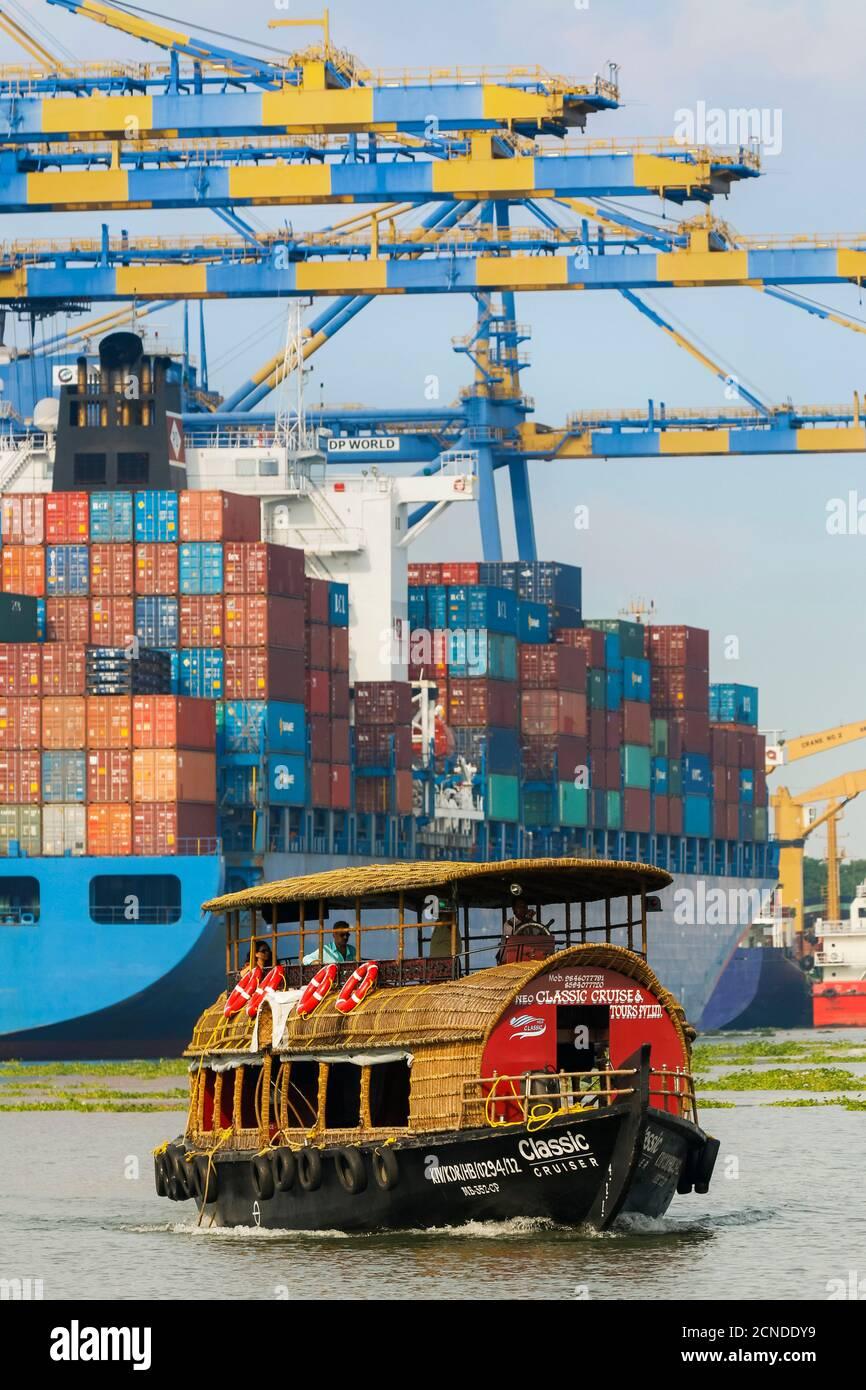 Tourist boat near container ship and cranes at Vallarpadam Container Terminal, a major Indian port, Kochi (Cochin), Kerala, India, Asia Stock Photo