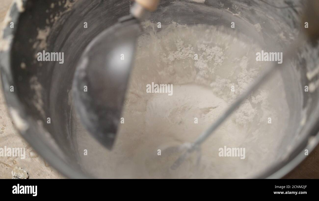 Mix the solution in a bucket using a construction mixer. Worker mixing plaster in a bucket for alignment and putty walls of the apartment using an Stock Photo