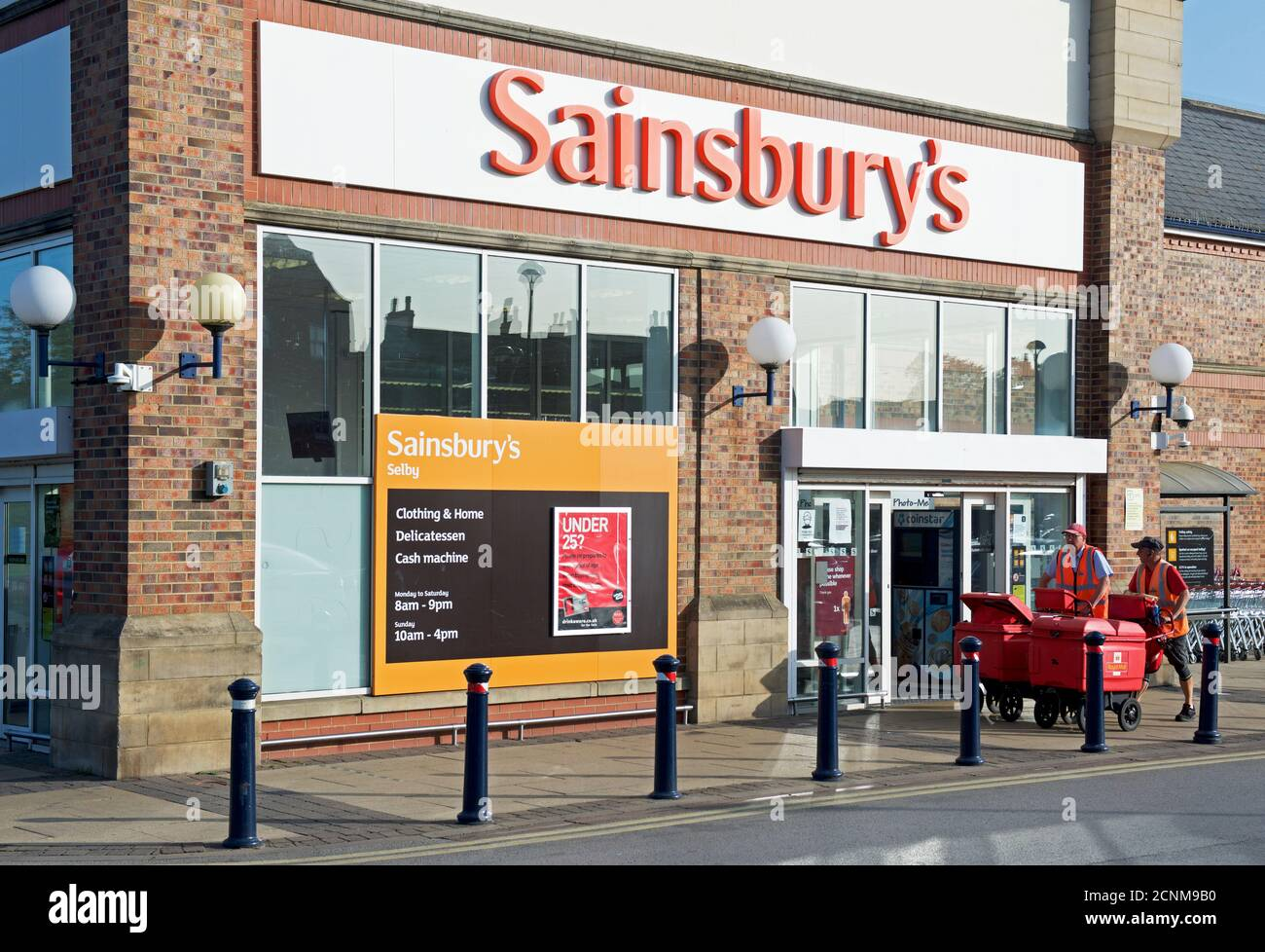 Postmen passing the entrance of Sainsbury's supermarket in Selby, North Yorkshire, England UK Stock Photo