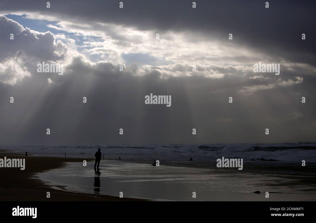 A person stands on the shores of the Mediterranean Sea on a stormy day at Nitzanim beach, near the southern city of Ashkelon, January 7, 2013. REUTERS/Amir Cohen (ISRAEL - Tags: ENVIRONMENT TRAVEL TPX IMAGES OF THE DAY) Stock Photo