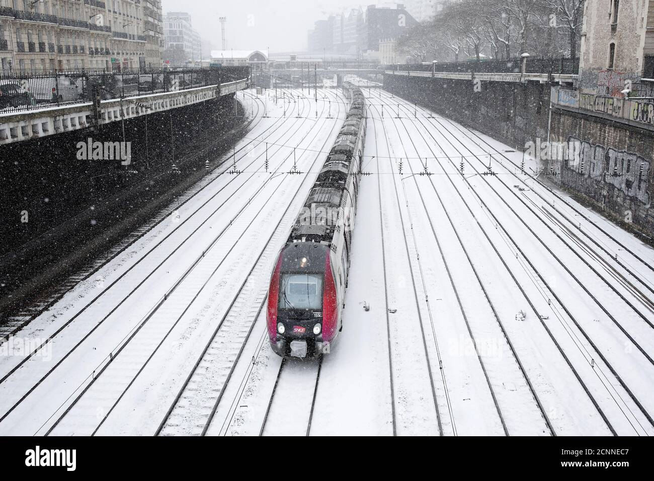 A train of French state-owned railway company SNCF and railroad tracks are seen under the falling snow at Pont-Cardinet railway station in Paris as winter weather bringing snow and freezing temperatures continues in France, February 9, 2018. REUTERS/Benoit Tessier Stock Photo