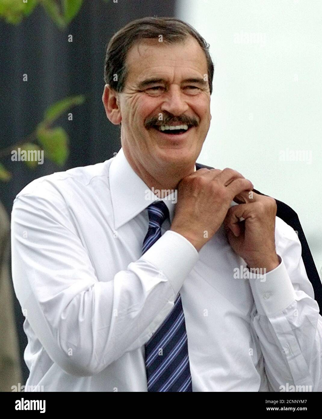 Mexican President Vicente Fox laughs after his arrival at Quintos de Mora near Toledo, where he was received by Spanish Prime Minister Jose Maria Aznar October 13, 2001. Fox is on a four-day official state visit to Spain. REUTERS/Andrea Comas  AC Stock Photo