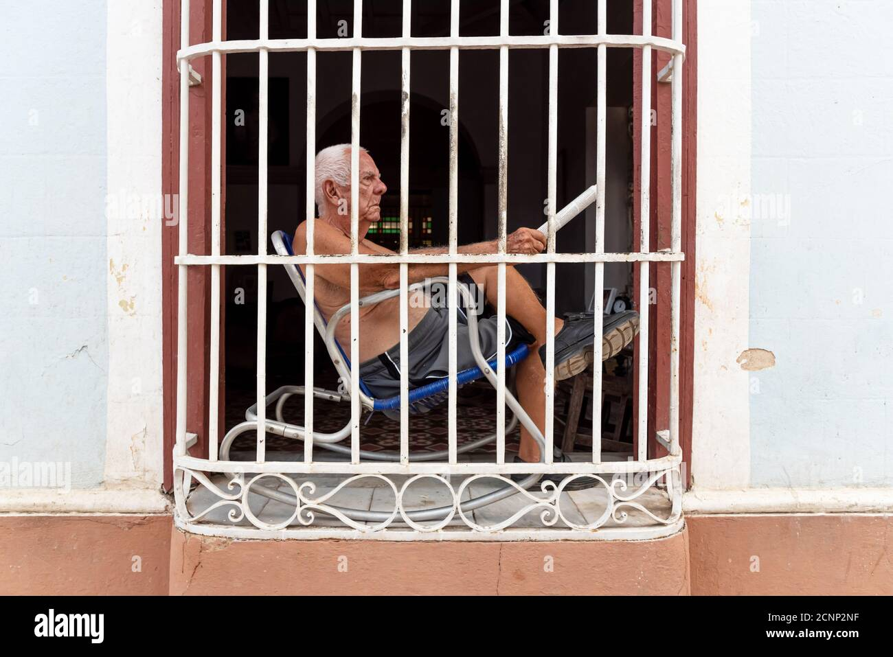August 26, 2019: Man sitting in front of his window with bars. Trinidad, Cuba Stock Photo
