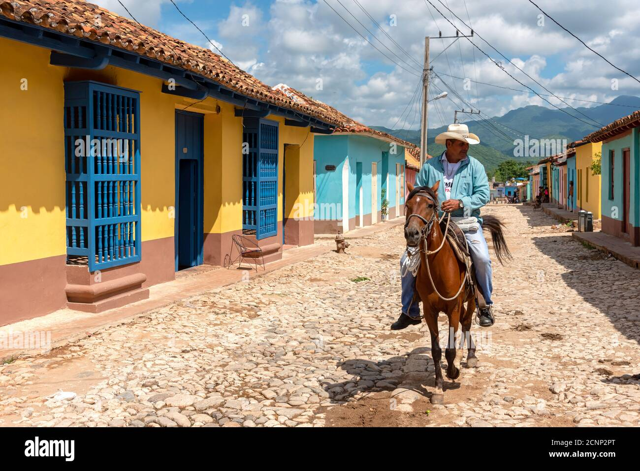 August 24, 2019: Man riding horse in the colored streets of Trinidad. Trinidad, Cuba Stock Photo
