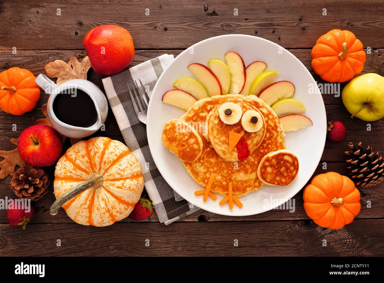 Thanksgiving breakfast table scene with turkey pancakes. Top view against a rustic wood background. Stock Photo