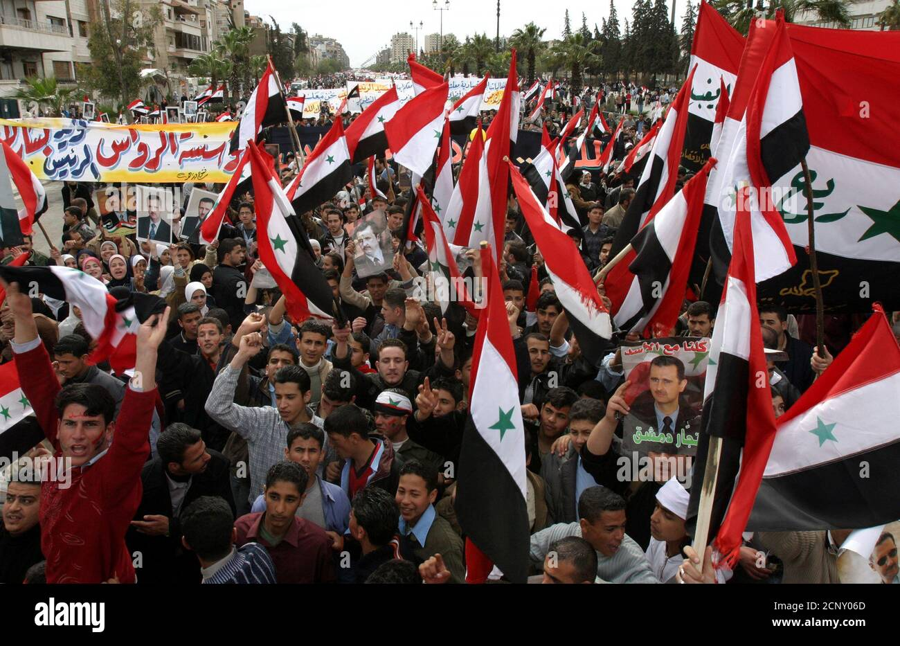 """Tens of thousands of Syrians wave flags during a rally in support of Syria's President Bashar al-Assad, who is facing international pressure over neighbouring Lebanon, in central Damascus March 9, 2005. """"With our souls and blood we sacrifice ourselves for Assad,"""" chanted the crowds, waving Syrian flags and carrying pictures of their young president, who has pledged to pull his troops out of Lebanon following weeks of anti-Syrian protests in Beirut. REUTERS/Khaled al-Hariri  kh/CCK Stock Photo"""