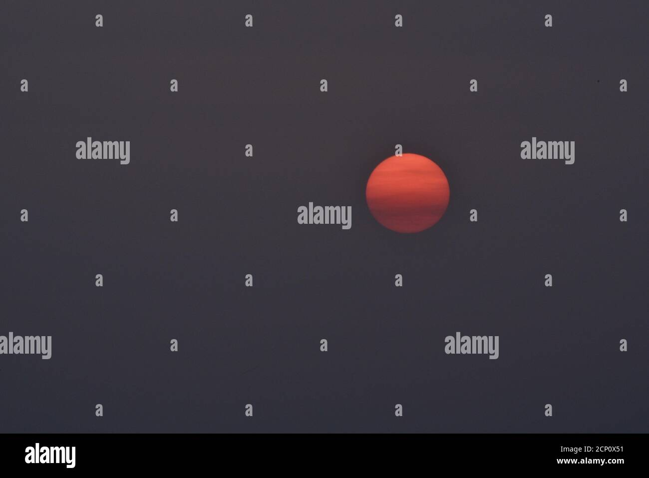 Hazy, smoke-filled sky from California and Oregon wildfires, with surreal, setting sun (no clouds) pasted in ominous sky, Browntown, Wisconsin, USA Stock Photo