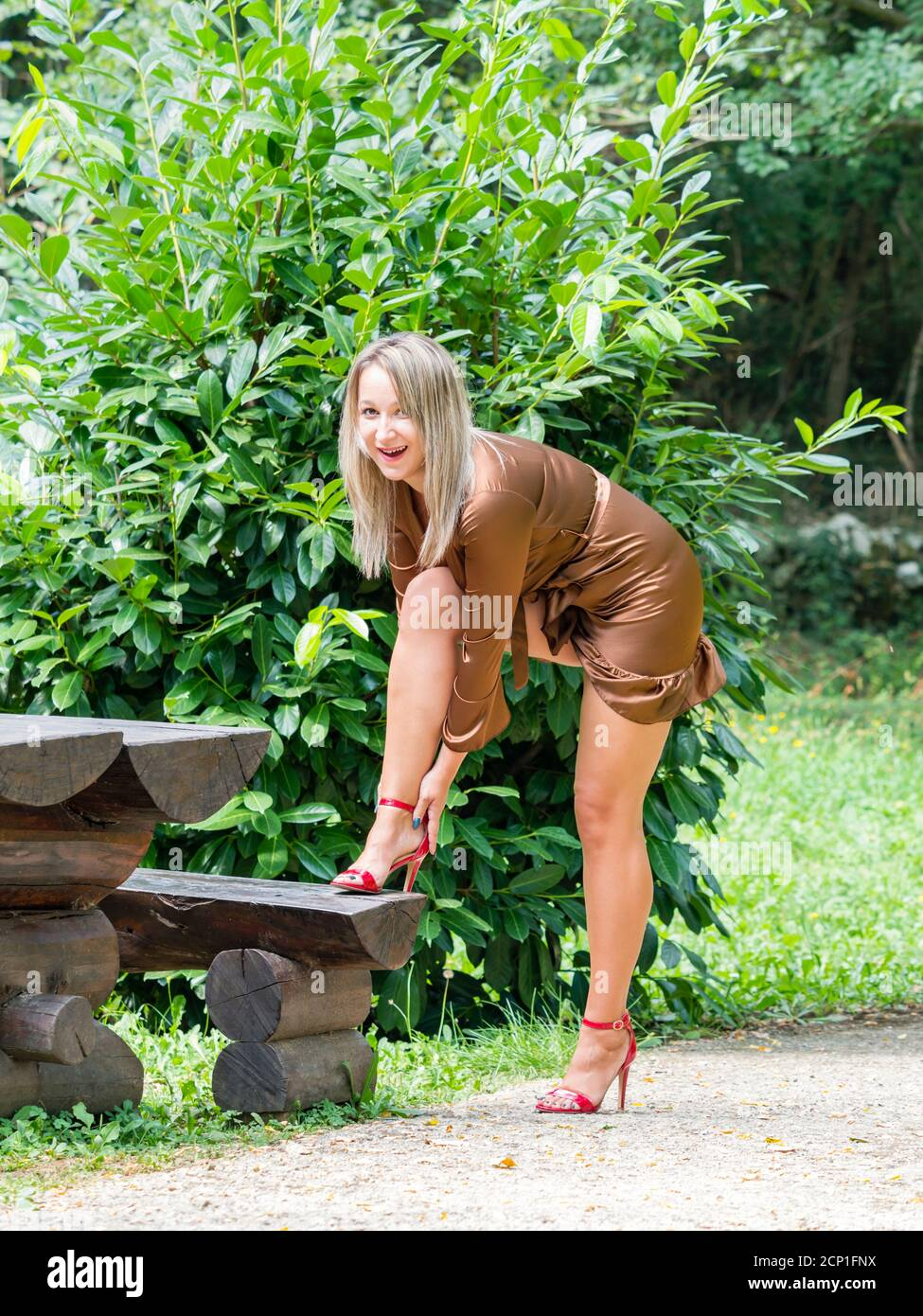 Stiletto heels legs young woman buckling buckle tying Red high-heels tie laces standing in park raising leg on wooden bench happy to see smiling smile Stock Photo