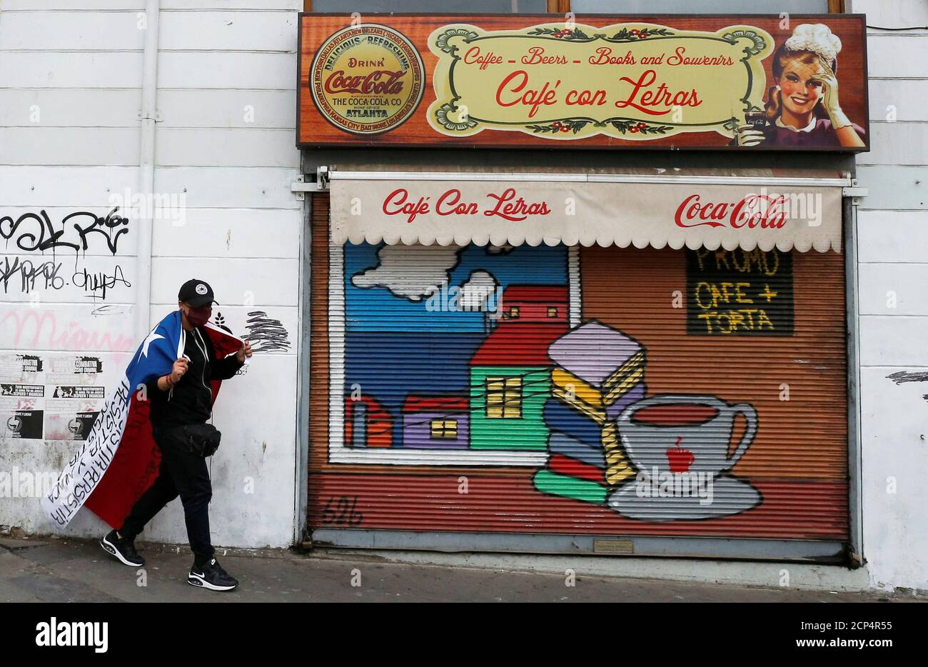 A waiter walks next to a cafe closed after losing his job due to the mandatory closure of all restaurants, cafes and bars as a precaution against the spread of the coronavirus disease (COVID-19) in Valparaiso, Chile  April 9, 2020. Picture taken April 9, 2020.  REUTERS/Rodrigo Garrido Stock Photo