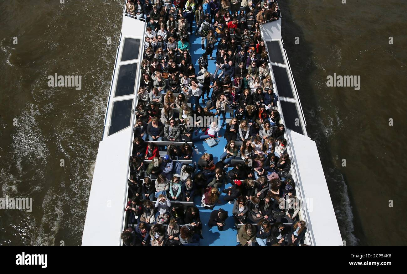 People sit in an open top boat as they cruise on the River Thames in London, Britain May 15, 2016. REUTERS/Neil Hall Stock Photo