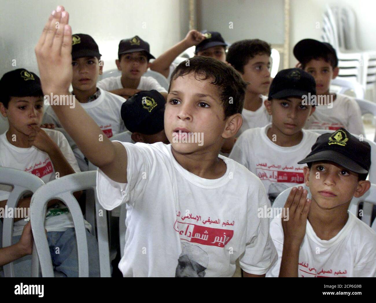 """A Palestinian boy wearing a T-Shirt bearing the words """"The Islamic summer camp"""" attends a summer camp run by the Islamic Jihad in Gaza July 16, 2002. Summer camps for Palestinian children dropped weapons training this year after a parental uproar over child suicide bombers. But some camps, mainly Islamic ones, still preached the idea of destroying Israel and at least one handed out toy rifles to children for an exercise in attacking a model in miniature of a Jewish settlement in occupied territory. TO GO WITH STORY BC-MIDEAST-PALESTINIANS-CAMPS REUTERS/Suhaib Salem  SJS/CLH/ Stock Photo"""