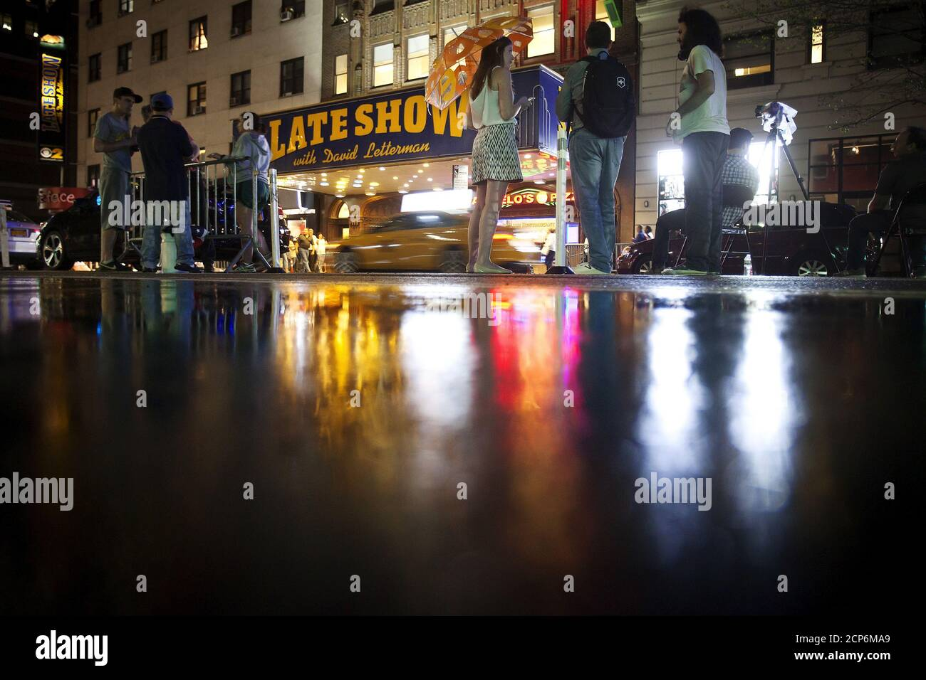 """People stand and wait for a sign crew to remove the marquee across the street from the Ed Sullivan Theater where """"The Late Show"""" with David Letterman used to tape in the Manhattan borough New York May 27, 2015. The taping and broadcast of the final edition of """"The Late Show"""" was May 20, and workers are now slowly transforming the theater for the show's new host Stephen Colbert which will premiere on September 8, 2015.   REUTERS/Carlo Allegri Stock Photo"""