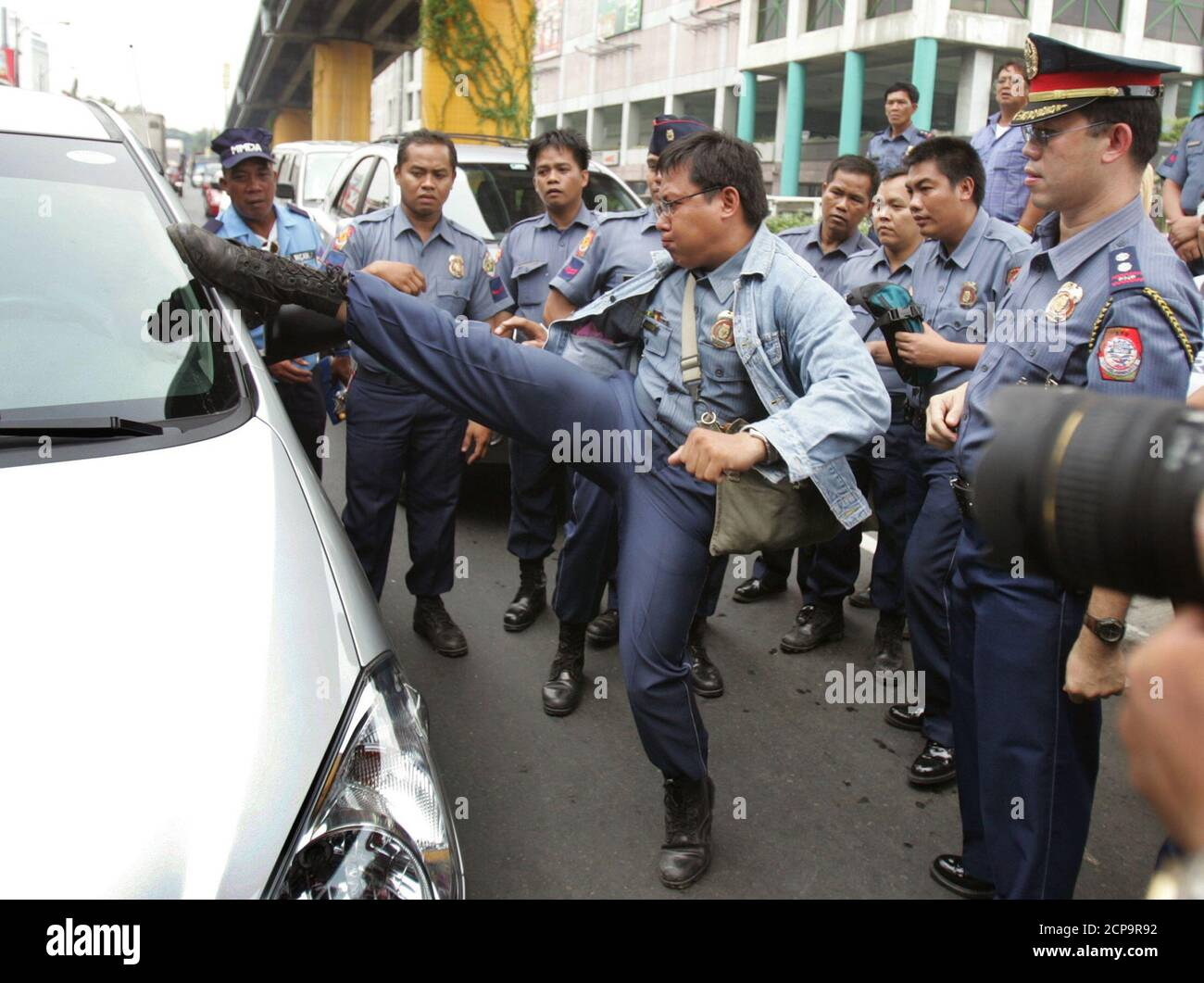 A Filipino police officer tries to kick open the window of a car whose driver had lost consciousness near the EDSA shrine in Manila.  A Filipino police officer tries to kick open the window of a car whose driver had lost consciousness near the EDSA (Epifanio de los Santos Avenue) shrine in Manila July 23, 2005. Police had converged at the shrine, the site of the 1986 and 2000 People Power uprising, to monitor an anti-Arroyo march. REUTERS/Adrees Latif Stock Photo