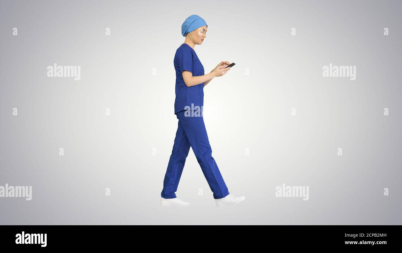 Female doctor or nurse in blue uniform using her phone as she wa Stock Photo
