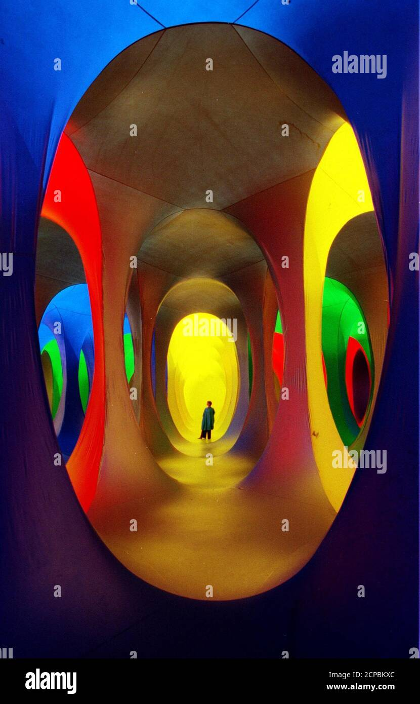 An artists assistant examines the inflatable interactive sculpture entitled 'Dreamspace' on Shepherd's Bush Green in London, July 25. The large inflatable network of coloured tunnels was created by artist Maurice Agis, and participants are encouraged to wear coloured overalls as they wander through the structure to the accompaniment of ambient music.  BRITAIN Stock Photo