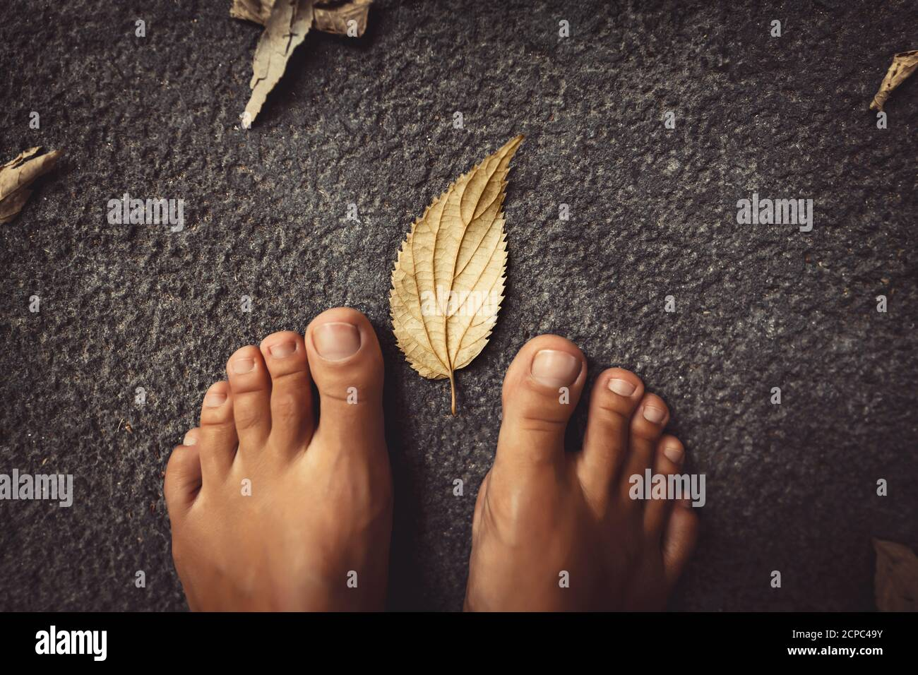 Welcome Fall Background. Closeup Concept Photo of a Barefoot Women Feet and Dry Leaves. Autumn Season Theme. Stock Photo