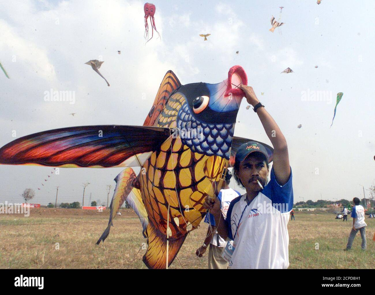 An Indonesian participant prepares to fly a kite shaped like a fish in Jakarta June 30, 2002. The men are among dozens of international participants at Jakarta's international kite festival. Eleven countries and dozens of provinces in Indonesia will take part in the three-day festival. REUTERS/Supri  AS/DL Stock Photo