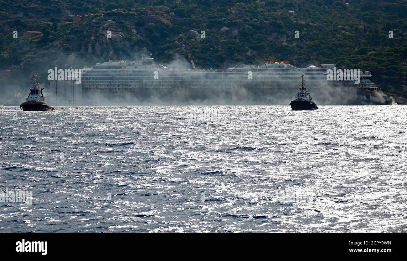 Black smoke comes out from the back of the Costa Concordia cruise liner during its refloat operation at Giglio harbour July 22, 2014. The massive hulk of the Costa Concordia is nearly ready to be towed away from the Italian island where it struck a rock and capsized two-and-a-half years ago, killing 32 people, officials said on Sunday. The 114,500-tonne Concordia has been slowly lifted from the sea floor since Monday, when salvagers began pumping air into 30 large metal boxes, or sponsons, attached around the hull. A convoy of 14 vessels will then tow the Concordia to a port near Genoa, where  Stock Photo