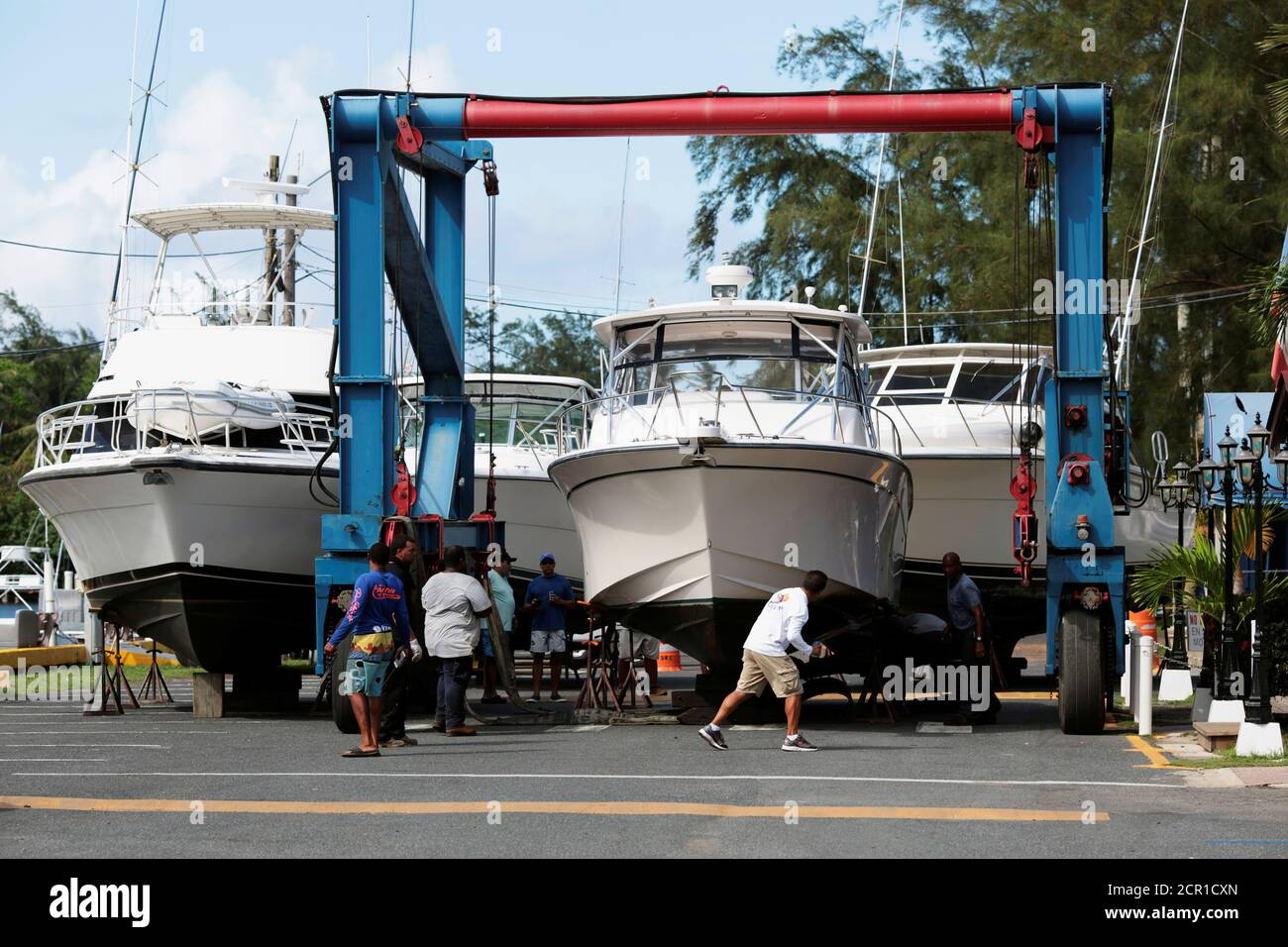 Workers put boats on dry docks in preparation, as Hurricane Irma, barreling towards the Caribbean and the southern United States, was upgraded to a Category 4 storm, in San Juan, Puerto Rico September 4, 2017. REUTERS/Alvin Baez Stock Photo