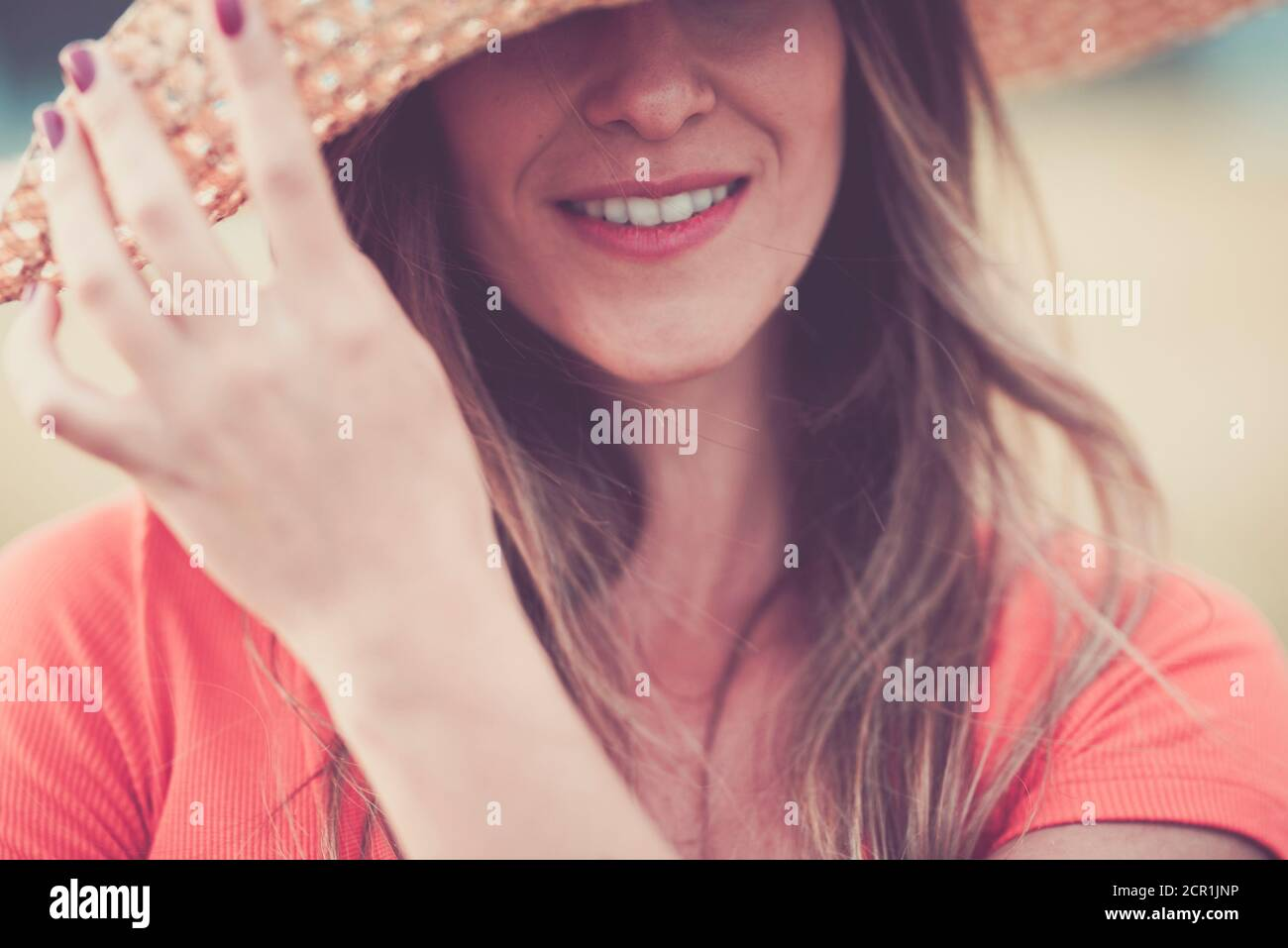 Close up woman portrait in vintage pink tones with cheerful and happy hidden eyes young caucasian lady with long beautiful hair and hat - concept of Stock Photo