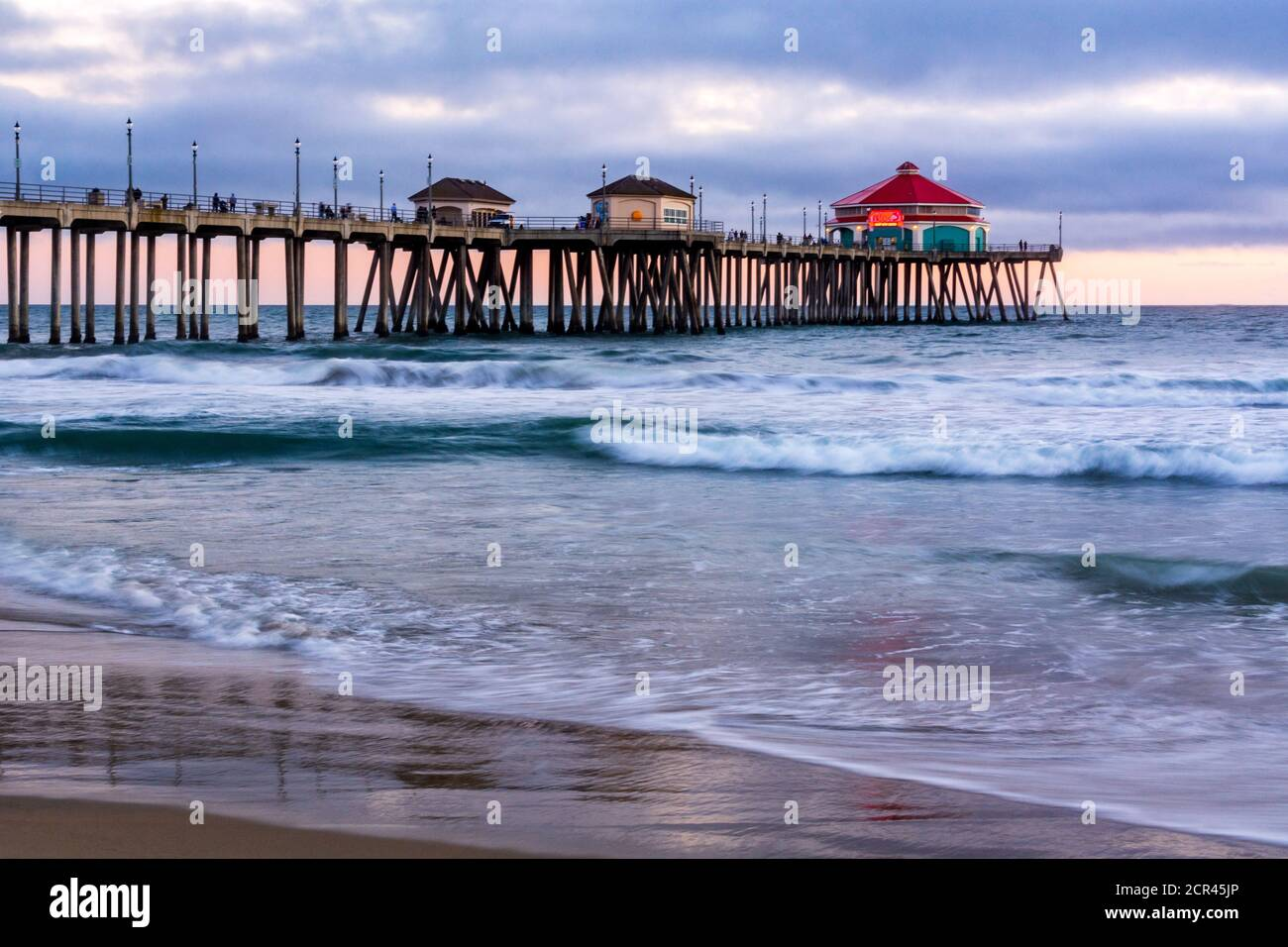 Seascape of the Huntington Beach pier at sunset, with slow shutter speed. Ruby's Diner is located at the end of the pier and is popular with tourists. Stock Photo