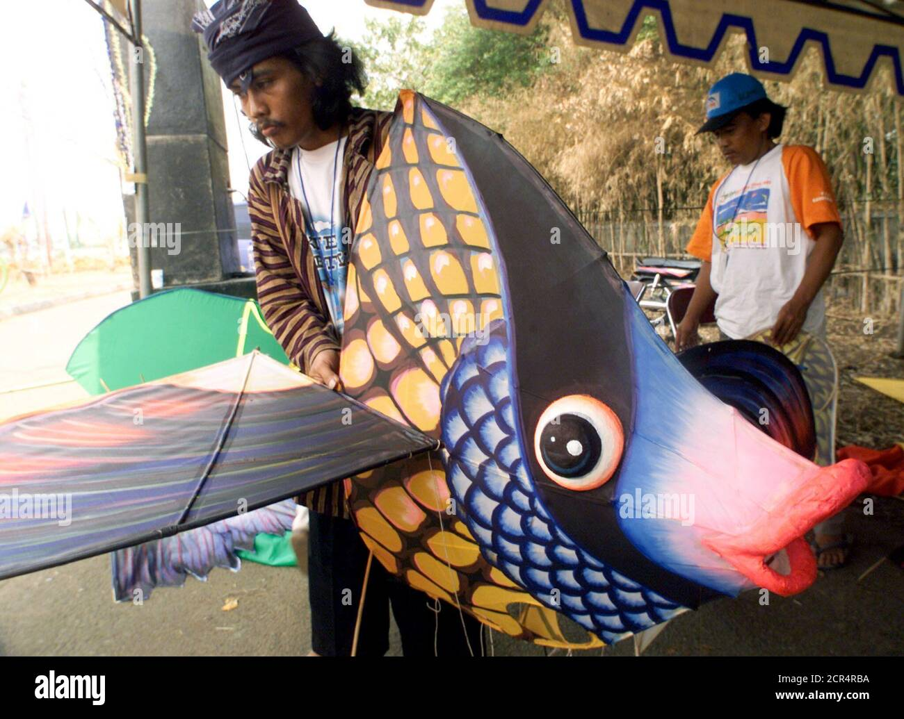Indonesian men prepare a kite shaped like a fish for a kite festival in Jakarta on June 28, 2002. The men are among dozens of international participants at Jakarta's international kite festival. Eleven countries and dozens of provinces in Indonesia will take part in the three-day festival. REUTERS/Supri  DW/CP Stock Photo