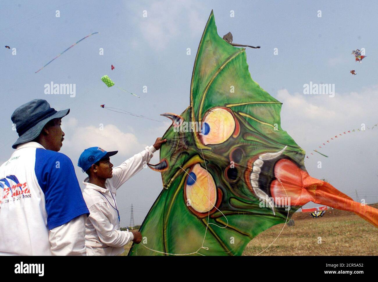 Indonesian participants prepare to fly a kite shaped like a monster's face in Jakarta June 30, 2002. The men are among dozens of international participants at Jakarta's international Kite festival. Eleven countries and dozens of provinces in Indonesia will take part in the three-day festival. REUTERS/Supri  AS Stock Photo