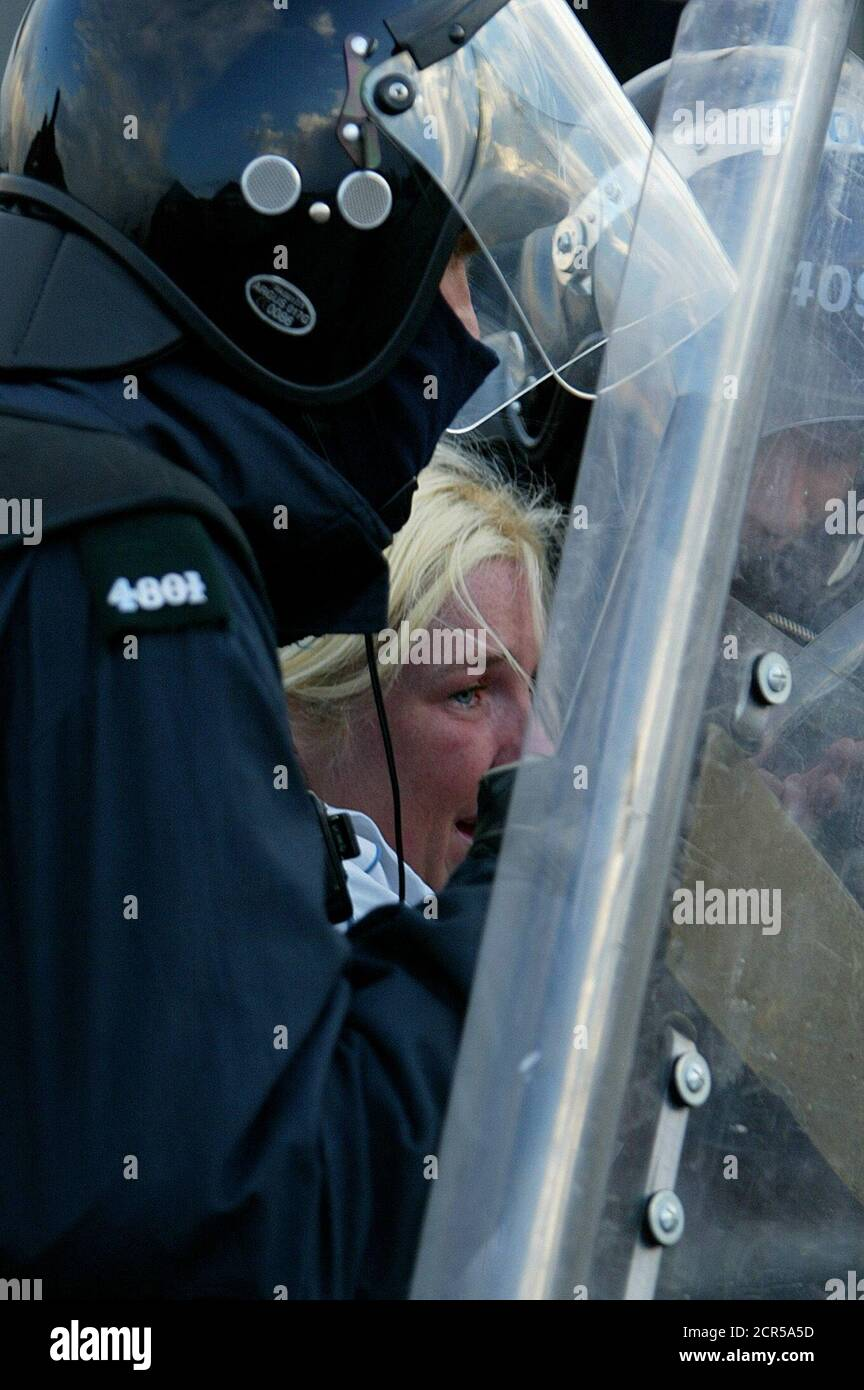 An Orange woman is helped by police as the parade marches through the Catholic area of Ardoyne July 12, 2002. The two marches passed through the contentious areas of Ardoyne and the Springfield road with minor unrest. REUTERS/Kieran Doherty  KD/CRB Stock Photo