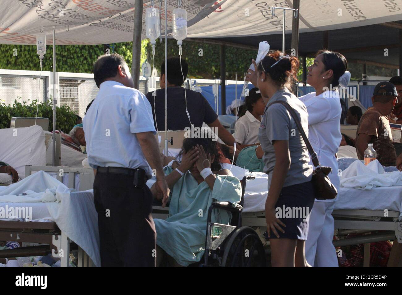 A patient in a wheelchair is attended to by a nurse at a makeshift emergency room after being evacuated from a hospital damaged by an earthquake on Tuesday in Ometepec in the Mexican state of Guerrero March 20, 2012. The 7.4-magnitude quake hit hardest in the southwestern state of Guerrero, where around 800 houses were damaged, officials said. The state governor Angel Aguirre said he had reports of homes being knocked down, though state authorities could not confirm this. REUTERS/Jacob Garcia (MEXICO - Tags: DISASTER) Stock Photo