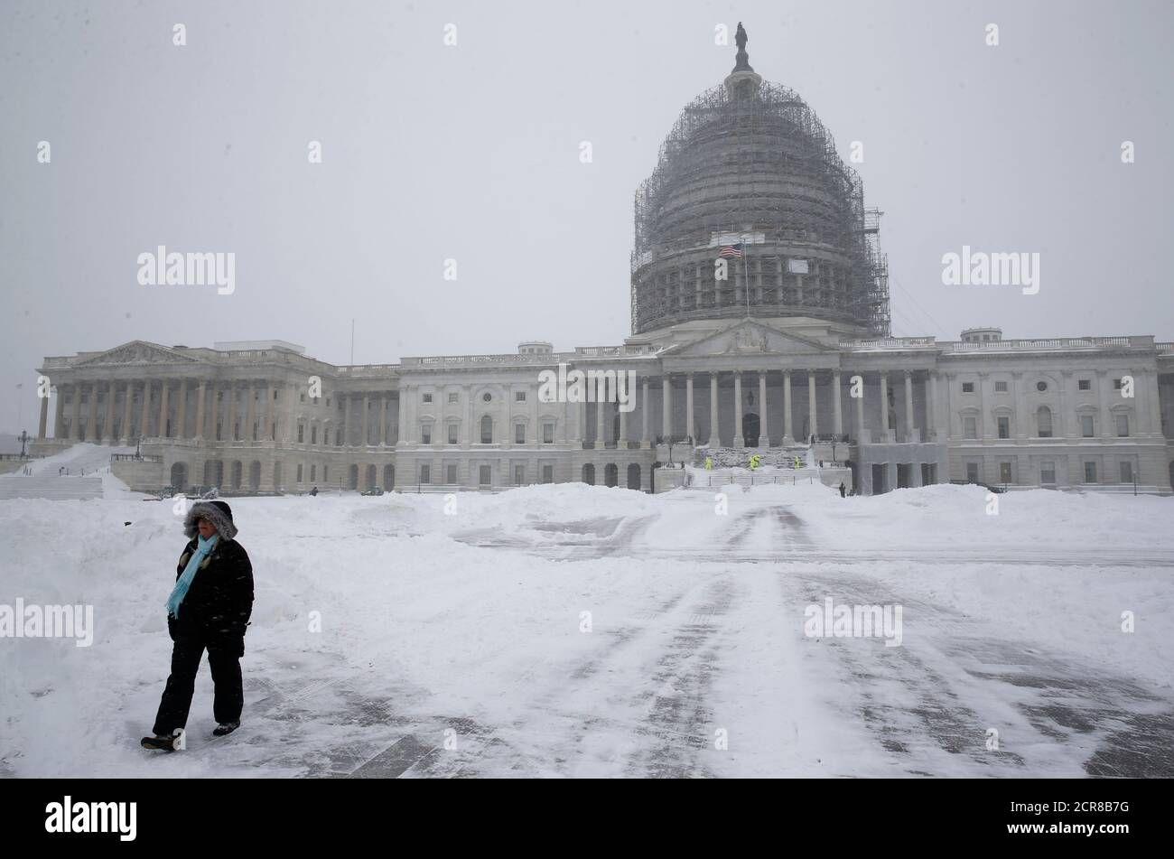 A person walks on the snow-covered grounds of the U.S.Capitol in Washington January 23, 2016. Thick snow covered the Washington, D.C. area on Saturday as a potentially record-breaking blizzard paralyzed road, rail and airline travel on the U.S. East Coast from North Carolina to New York. REUTERS/Jonathan Ernst Stock Photo