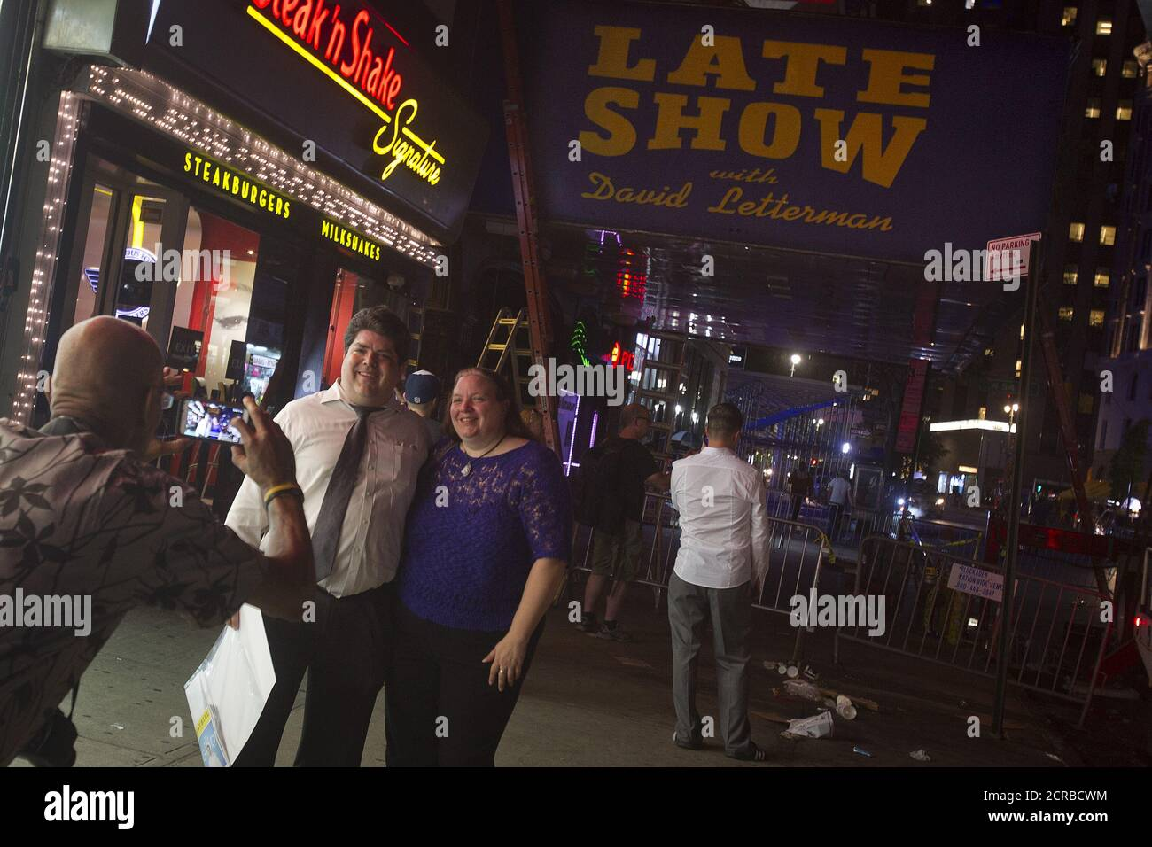"""People pose for a photo as workers remove the marquee from the Ed Sullivan Theater where """"The Late Show"""" with David Letterman used to tape in the Manhattan borough New York May 27, 2015. The taping and broadcast of the final edition of """"The Late Show"""" was May 20, and workers are now slowly transforming the theater for the show's new host Stephen Colbert which will premiere on September 8, 2015.   REUTERS/Carlo Allegri Stock Photo"""