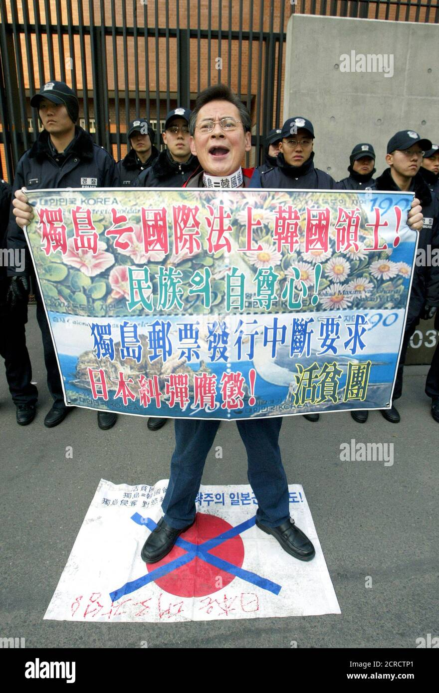 Holding a sign depicting a new Korean postal stamp of a disputed island claimed by South Korea and Japan, a South Korean protester shouts anti-Japan slogans in front of the Japanese embassy in Seoul January 9, 2004. South Korea's postal service announced on Thursday it will issue on January 16 four kinds of stamps depicting birds and plants on Dokdo island. Tokyo has asked Seoul to scrap the stamps. Both countries have been wrangling over Dokdo, which Japan calls Takeshima, for centuries. It is situated halfway between Korea and Japan in the East Sea. The islets,off the eastern tip of Ullung I Stock Photo