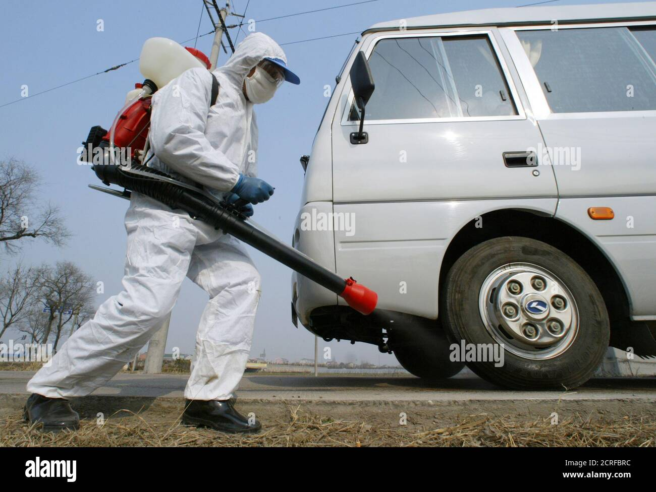 A health worker disinfects a vehicle passing Nanhui district, near the farm where bird flu case was reported on the outskirts of Shanghai, February 13, 2004. China on Friday reported outbreaks of bird flu in Shanghai and three other regions as the World Health Organisation said it could not rule out the possibility of human infection in the country. Fourteen of China's 31 provinces and major cities have confirmed outbreaks of the avian influenza that has killed 14 Vietnamese and five Thais and led to the culling of millions of poultry in eight Asian countries. REUTERS/Claro Cortes IV  CC/FA Stock Photo