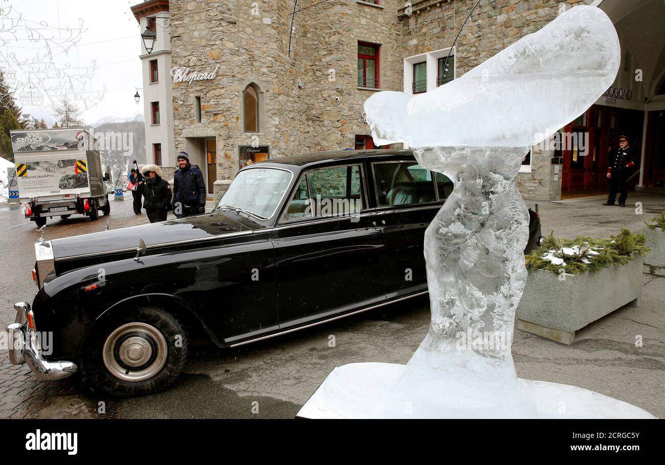 """A huge ice sculpture of the """"Spirit of Ecstasy"""", the bonnet ornament of Rolls-Royce cars, also known as """"Emily"""",  stands in front of a vintage Rolls-Royce Phantom car in the mountain resort of St. Moritz, Switzerland February 2, 2017.  REUTERS/Arnd Wiegmann Stock Photo"""